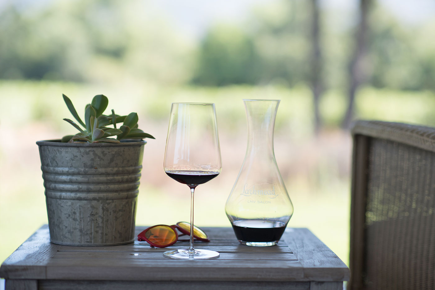 A glass of wine, decanter, sunglasses and a potted succulent sit on a table on Lark Room porch